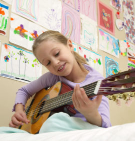 Girl (5-7) playing acoustic guitar on bed, low angle view