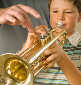Boy playing trumpet with instructor